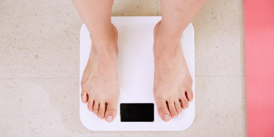 Jeune femme au régime qui se pèse pour voir si elle a perdu du poids