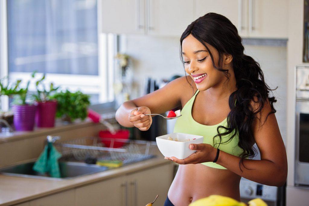Jeune femme au régime qui se fait plaisir en mangeant un plat sain mais gourmand