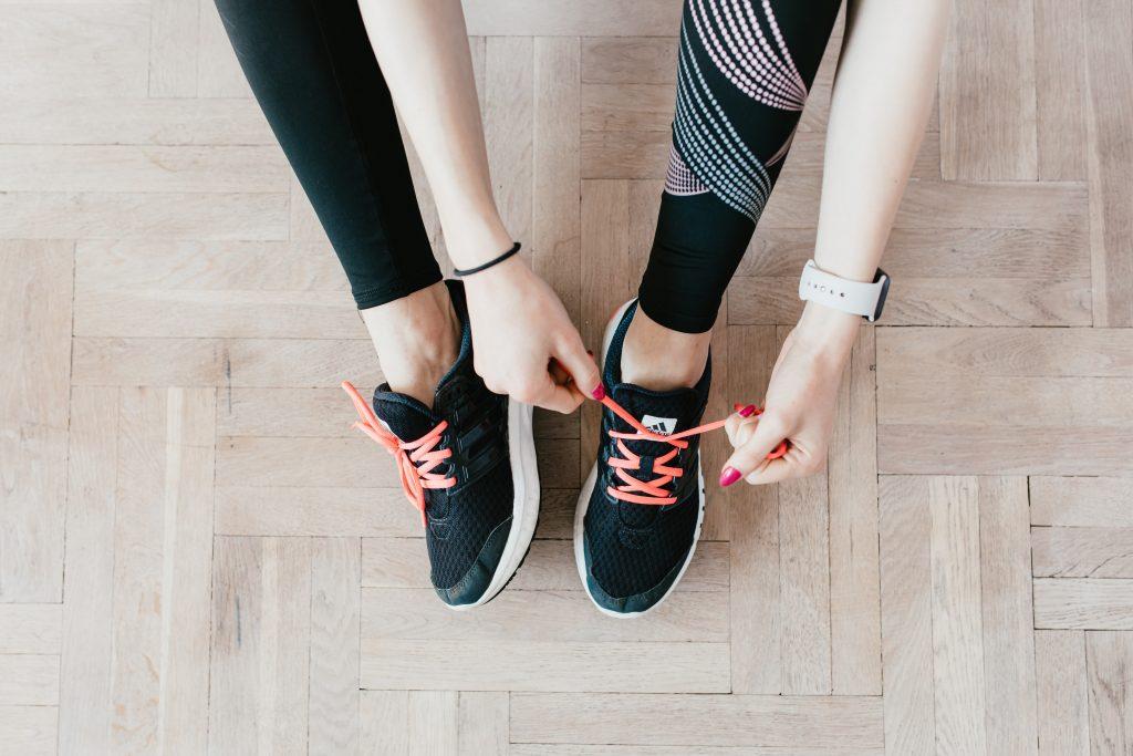 Jeune femme qui enfile ses baskets pour faire du sport et mincir